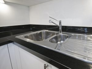 stainless steel kitchen sink detail on black granite worktop